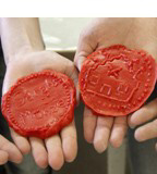 The hands of pupils holding roman coins made of wax.