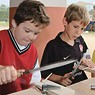 Two students carving bones during the Roman Weekends.""