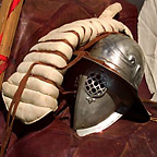 Close-up of a gladiator's equipment including a helmet and a padded arm-guard.