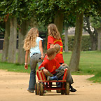 Two girls pulling a small wagon in which two other children are sitting.