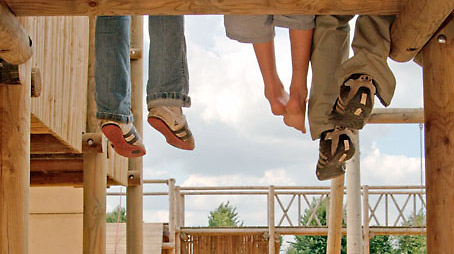 Three children dangle their legs from a climbing frame on the playground of the park.