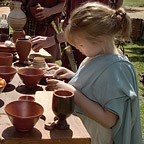 A young girl in a light blue Roman dress is looking at Roman pots.
