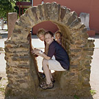 Three children are sitting in the ruins of a genuine Roman aqueduct.