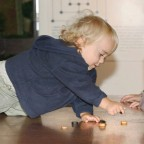 Toddler crawling over a table with Roman board games.