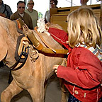 "A girl touches the wooden model of a horse in the themed pavilion ""Travel & traffic""."