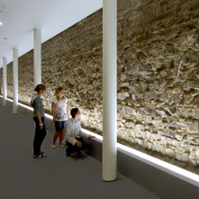 Three teenagers looking at an antique wall within the RömerMuseum.