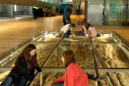 Children looking at the traces through the glass floor of the RömerMuseum.