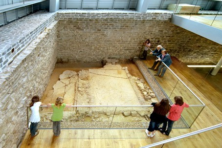 Visitors looking at an excavation site within the museum.