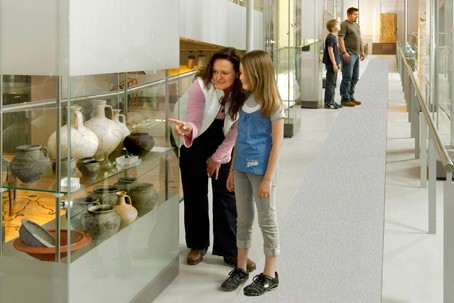Mother and daughter looking at Roman pots in a glass cabinet.