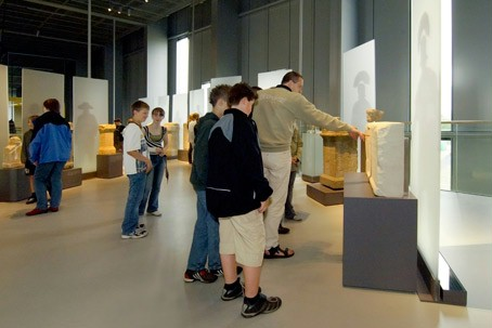 Children and adults looking at exhibits in the RömerMuseum.