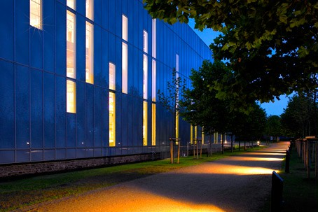The illuminated outer wall of the RömerMuseum in the evening.