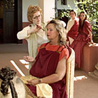 Hairdresser dressing the hair of a woman wearing Roman robes.