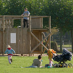 Man relaxing on the lawn next to a baby carriage with children playing on the large timber adventure playground in the background.