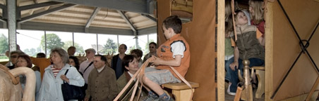 Children exploring a reconstructed Roman carriage.
