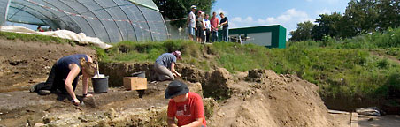Excavation team unearthing a Roman foundation wall under the eyes of a group of visitors.