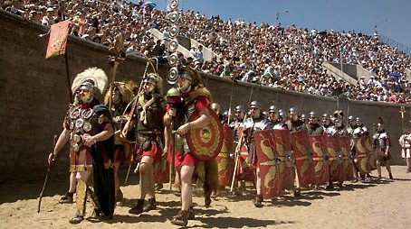 A group of roman soldiers marching into the arena of the amphitheater.