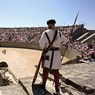 A man in the uniform of a roman gladiator stands at the entrance oft the amphitheater.