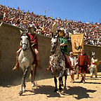 Two gladiators riding into the arena in front of packed stands, followed by actors holding a banner.