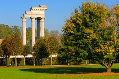 View over a lawn with autumn trees on the partially reconstructed harbour temple.