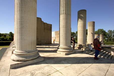Visitors looking at the partially reconstructed harbour temple with its high pillars.