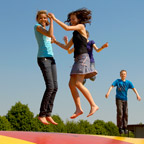 Youths jumping on a big, colourful bouncy pillow.