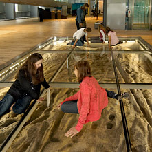 Children sitting on a pane of glass covering imprints of Roman feet.