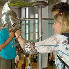 A little boy puts on a roman helmet.