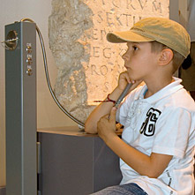 A boy listens to the stories told in the LVR-RömerMuseum